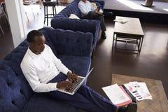 Hombres de negocios que trabajan en los sofás en el área de la relajación de la oficina Imagen de archivo