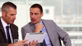 Hombres de negocios que trabajan en una tableta almacen de metraje de vídeo