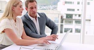 Hombres de negocios que trabajan junto en el ordenador portátil almacen de video