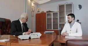 Hombres de negocios que trabajan junto en un documento durante una reunión en una oficina metrajes
