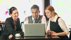 Hombres de negocios que trabajan junto mientras que comiendo café en un restaurante metrajes