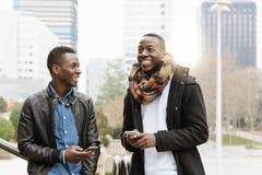 Hombres de negocios que usan el móvil en la calle Imagenes de archivo