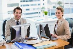 Hombres de negocios que usan el ordenador mientras que mira la cámara Fotos de archivo