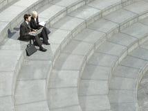 Hombres de negocios que usan el ordenador portátil en las escaleras espirales Imagen de archivo