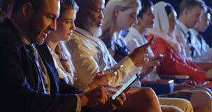Hombres de negocios que usan el teléfono móvil mientras que se sienta en asientos en el auditorio 4k almacen de video