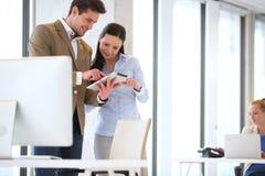 Hombres de negocios que usan la tableta con el colega femenino en fondo en la oficina imagen de archivo libre de regalías