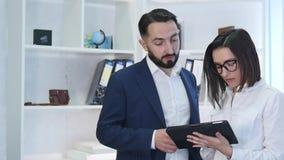Hombres de negocios que usan la tableta con el colega femenino en fondo en la oficina almacen de metraje de vídeo