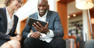 Hombres de negocios que usan la tableta digital en el pasillo del hotel imágenes de archivo libres de regalías