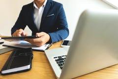 Hombres de negocios que usan la tableta para estudiar los datos para el expansio del negocio fotografía de archivo