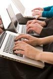 Hombres de negocios que usan las computadoras portátiles para hacer notas fotos de archivo