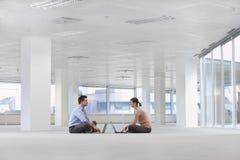 Hombres de negocios que usan los ordenadores portátiles en espacio de oficina vacío imagen de archivo