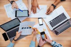 Hombres de negocios que usan los teléfonos móviles y los ordenadores portátiles para hacer informe Fotografía de archivo libre de regalías