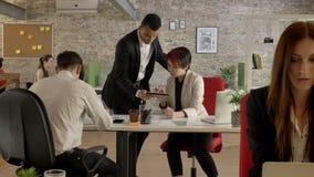 Hombres de negocios de raza mixta que trabajan en la oficina, hombre negro que viene a la mujer asiática y que habla sobre la tab almacen de video