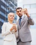 Hombres de negocios serios con las tazas de papel al aire libre Imágenes de archivo libres de regalías