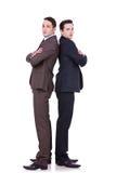 Hombres de negocios serios que se colocan de nuevo a la parte posterior Imagen de archivo libre de regalías