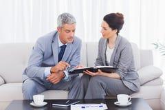 Hombres de negocios serios que trabajan y que hablan junto en el sofá Fotos de archivo libres de regalías