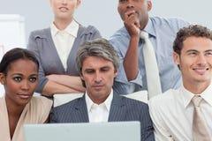 Hombres de negocios serios que usan una computadora portátil Imagenes de archivo