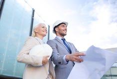 Hombres de negocios sonrientes con el modelo y los cascos Foto de archivo libre de regalías