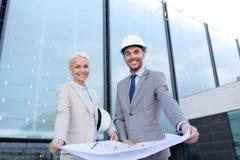 Hombres de negocios sonrientes con el modelo y los cascos Foto de archivo