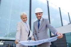 Hombres de negocios sonrientes con el modelo y los cascos Imagenes de archivo