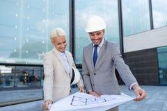 Hombres de negocios sonrientes con el modelo y los cascos Fotos de archivo libres de regalías