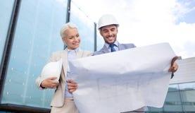 Hombres de negocios sonrientes con el modelo y los cascos Imagen de archivo libre de regalías