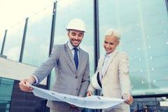 Hombres de negocios sonrientes con el modelo y los cascos Imágenes de archivo libres de regalías