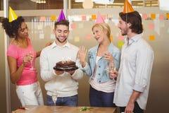 Hombres de negocios sonrientes con la torta de cumpleaños que disfrutan del partido Fotos de archivo libres de regalías