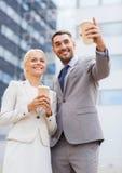 Hombres de negocios sonrientes con las tazas de papel al aire libre Imágenes de archivo libres de regalías