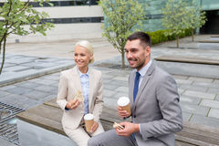 Hombres de negocios sonrientes con las tazas de papel al aire libre Fotos de archivo libres de regalías