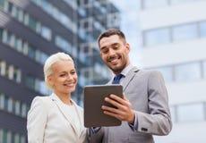 Hombres de negocios sonrientes con PC de la tableta al aire libre Imagen de archivo