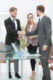 Hombres de negocios sonrientes felices que sacuden las manos después de un trato en offi imagen de archivo libre de regalías