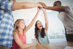 Hombres de negocios sonrientes que dan el alto cinco en el escritorio Imagen de archivo
