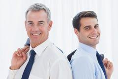 Hombres de negocios sonrientes que presentan de nuevo a la parte posterior junto mientras que lleva a cabo t Imágenes de archivo libres de regalías