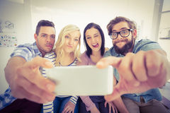 Hombres de negocios sonrientes que presentan para el selfie Foto de archivo