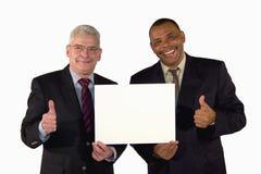 Hombres de negocios sonrientes que presentan una tarjeta del cuadro fotografía de archivo libre de regalías
