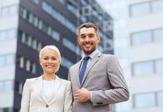 Hombres de negocios sonrientes que se colocan sobre el edificio de oficinas Imágenes de archivo libres de regalías