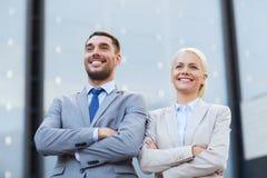 Hombres de negocios sonrientes que se colocan sobre el edificio de oficinas Fotografía de archivo