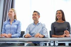 Hombres de negocios sonrientes que se encuentran en oficina imágenes de archivo libres de regalías