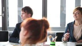 Hombres de negocios sonrientes que se sientan en la tabla en una reunión en la sala de conferencias metrajes