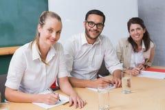 Hombres de negocios sonrientes que toman notas durante la reunión Foto de archivo