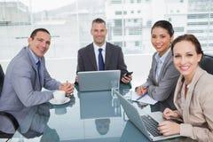 Hombres de negocios sonrientes que trabajan así como su ordenador portátil Imagen de archivo libre de regalías