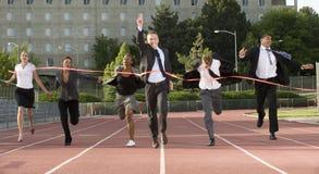 Hombres de negocios Sprinting a través de meta Fotos de archivo libres de regalías