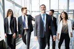 Hombres de negocios de Team Walking In Modern Office, hombres de negocios confiados y empresarias con el l?der maduro In Foregrou foto de archivo