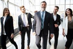 Hombres de negocios de Team Walking In Modern Office, hombres de negocios confiados y empresarias con el l?der maduro In Foregrou imagen de archivo