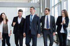 Hombres de negocios de Team Walking In Modern Office, hombres de negocios confiados y empresarias con el l?der maduro In Foregrou imágenes de archivo libres de regalías