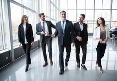 Hombres de negocios de Team Walking In Modern Office, hombres de negocios confiados y empresarias con el l?der maduro In Foregrou imagen de archivo libre de regalías