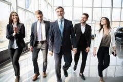Hombres de negocios de Team Walking In Modern Office, hombres de negocios confiados y empresarias con el l?der maduro In Foregrou fotos de archivo