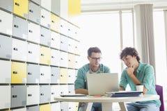 Hombres de negocios usando el ordenador portátil en la tabla en vestuario en la oficina creativa Fotografía de archivo libre de regalías