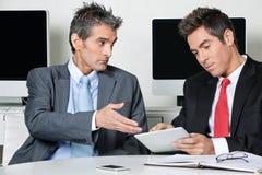 Hombres de negocios usando la tableta de Digitaces en el escritorio foto de archivo